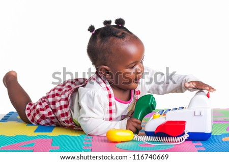A little girl having fun playing with a telephone on her letter carpet. - stock photo