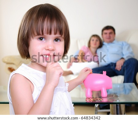 A little girl hides her money in the pig piggy bank. - stock photo