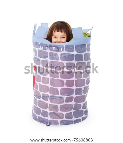 A little girl hides in the toy basket isolated on white background - stock photo