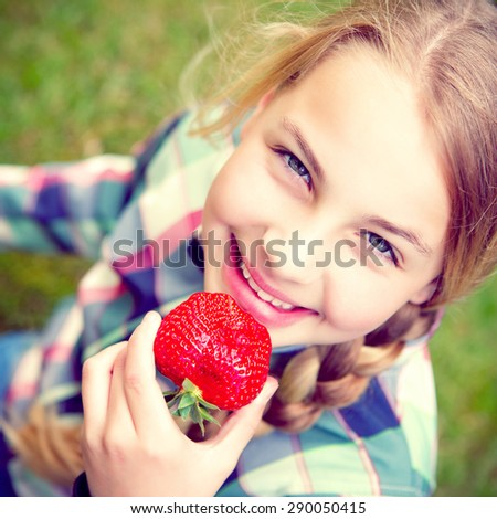 a little girl holding a strawberry near her mouth - stock photo