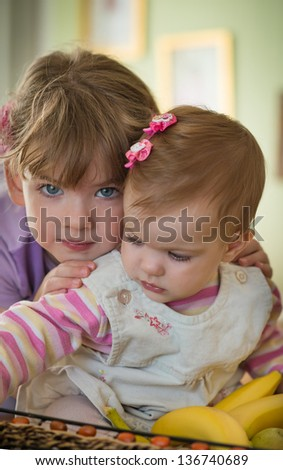 A little girl holding her baby sister - stock photo
