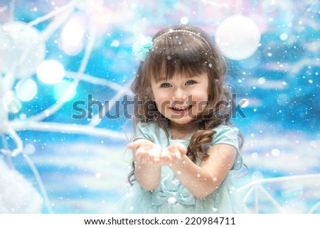 A little girl holding snow on blue background - stock photo
