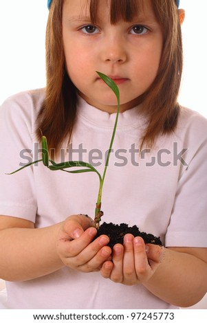 A little girl holds a plant in her hands with care - stock photo