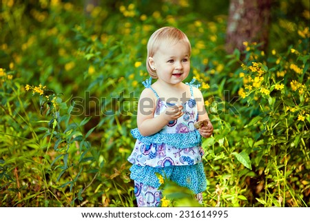 A little girl in a blue dress smiling while standing in the grass