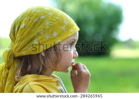 A little girl in a bright yellow bandanna eating a biscuit, close up - stock photo