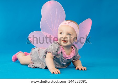 A little girl in a dress with wings