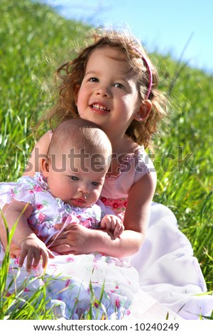 A little girl in a meadow holding her baby sister - stock photo