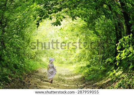 A little girl in a pink dress fun runs on the road in the fairy forest - stock photo