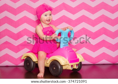 a little girl in a pink swim suit and cap on a toy car on pink background - stock photo