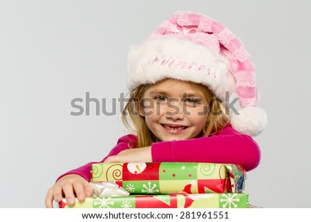A little girl in a studio environment with presents missing her two front teeth - stock photo
