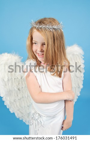 A little girl in a white angel costume.