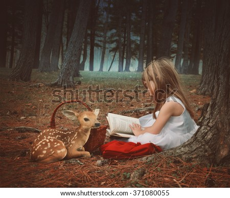 A little girl in a white dress is reading on old story book with a baby deer in the dark woods for an education or imagination concept. - stock photo