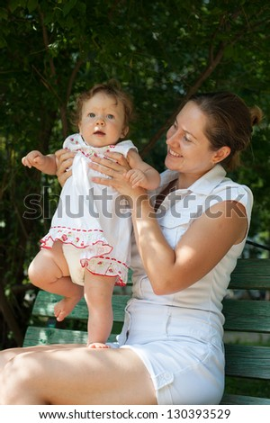 A little girl in a white sundress kneeling mom on a park bench - stock photo