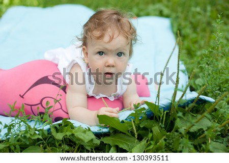 A little girl in a white sundress lying on the grass in the park - stock photo