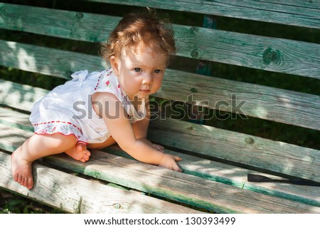 A little girl in a white sundress sitting on a park bench - stock photo