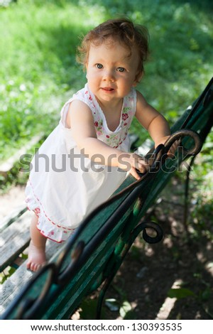 A little girl in a white sundress standing on a park bench