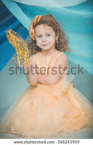 A little girl in a yellow dress with a magic wand - stock photo