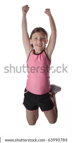 A little girl in athletic sporty clothing jumps in the air
