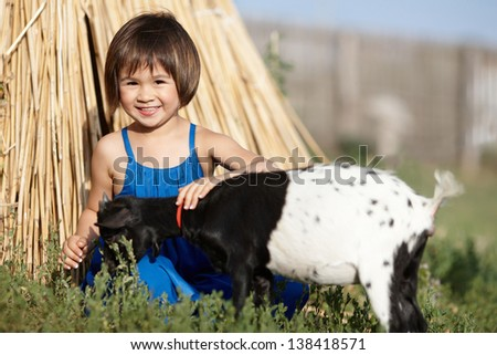 a little girl in blue dress with a goat