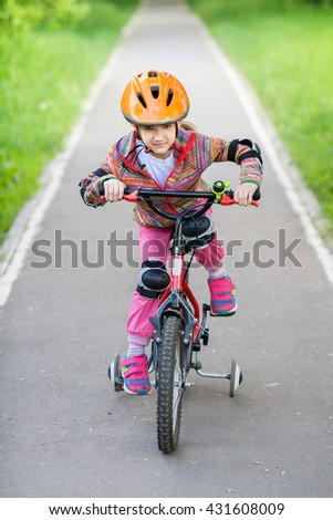 A little girl in helmet riding a Bicycle
