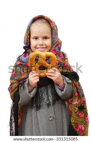 A little girl in traditional Russian kerchief with cracknel