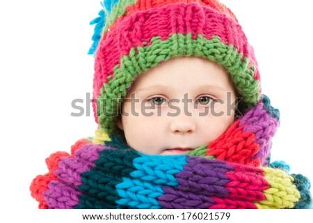 A little girl is cold and wrapped warm with a hat and scarf. - stock photo