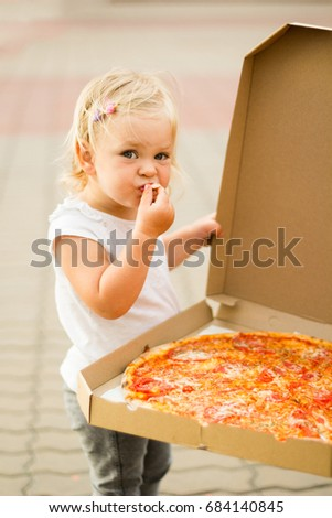 A little girl is eating pizza from a big box.