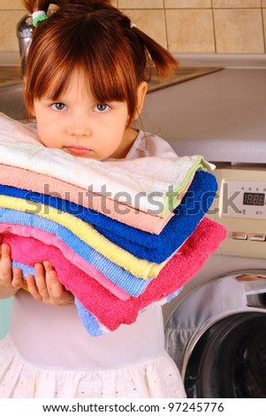 A little girl is going to wash the towels in the washing machine