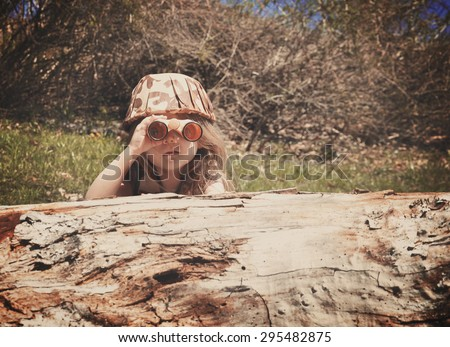 A little girl is hiding behind an old log in the woods with a camouflage hat and binoculars searching and playing for an imagination or exploration concept. - stock photo