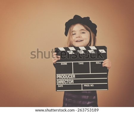 A little girl is holding an old retro film movie clapboard for a director or entertainment concept. - stock photo