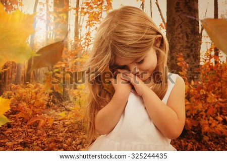 A little girl is holding onto a fall leaf in the woods with sunlight in the background and falling leaves for a season or nature concept - stock photo