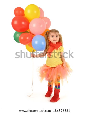 A little girl is holding rainbow helium party balloons on a white isolated background for a birthday or fun concept. The child is wearing a colorful tutu. - stock photo