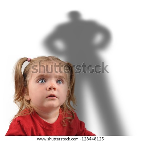 A little girl is looking up at a scary shadow of a man on a white background for a fear or kidnapping concept. - stock photo
