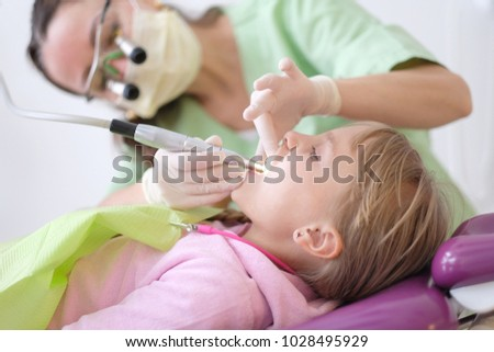 A little girl is lying in an armchair at a reception near a dentist