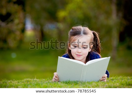 A little girl is lying on her stomach reading on the grass.  She has a look of enjoyment on her face and she looks very relaxed.  There is quite a bit of negative space around her.