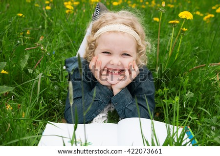 A little girl is lying on her stomach reading on the grass. She has a look of enjoyment on her face and she looks very relaxed.  - stock photo