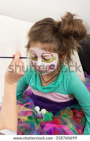 A little girl is painted as a clown - stock photo
