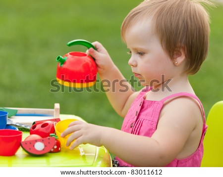 A little girl is playing a tea party - stock photo