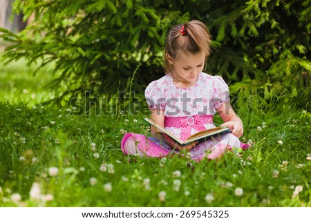 A little girl is  reading on the grass - stock photo