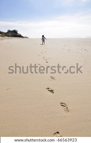 A little girl is running away on a wide, empty beach, leaving footprints. - stock photo