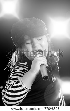 A little girl is singing into a microphone with flashes and lights in the background. - stock photo