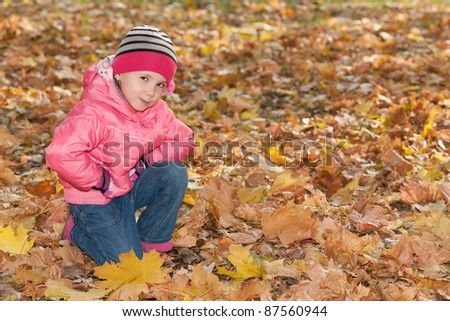 A little girl is sitting in the autumn park