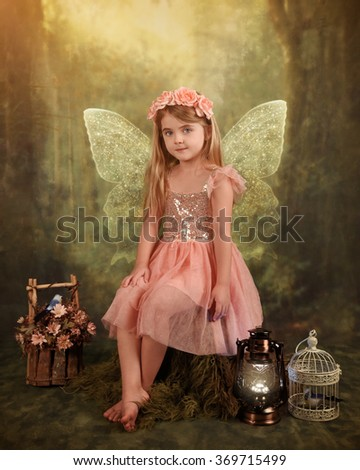 A little girl is sitting on a mushroom in the woods with sparkle fairy wings for an imagination or fairy tale concept.  - stock photo