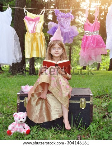 A little girl is sitting outside wearing a princess costume reading a story book with glasses on for an education or imagination concept. - stock photo