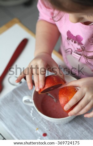 A little girl is squeezing blood orange juice into a bowl to make frosting