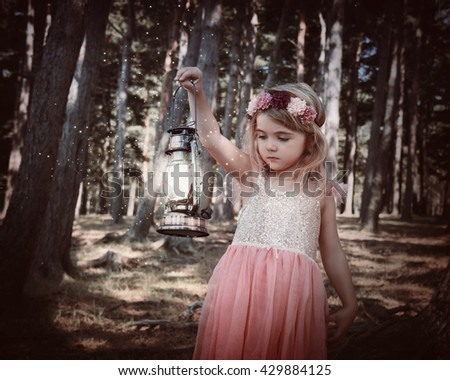 A little girl is standing in the woods with sparkle fairy magical dust on a lantern light for an imagination or fairy tale concept.  - stock photo