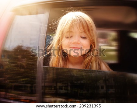 A little girl is sticking her head out the car window and looking down for a road trip or travel concept. - stock photo