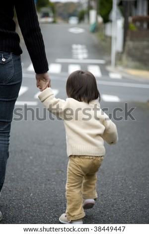 Little girl is walking down the street with her parents stock photo