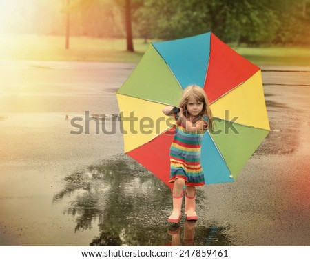 A little girl is walking with a rainbow umbrella in her hand and rubber boots outside at a park for a weather or season concept. - stock photo