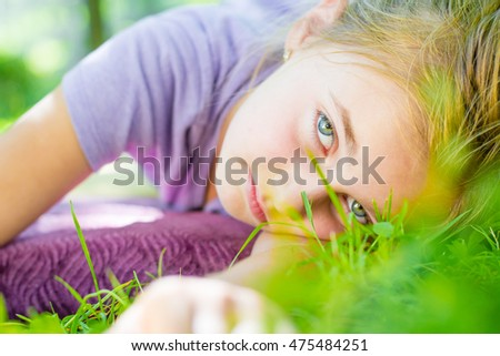 A little girl lay on a grass